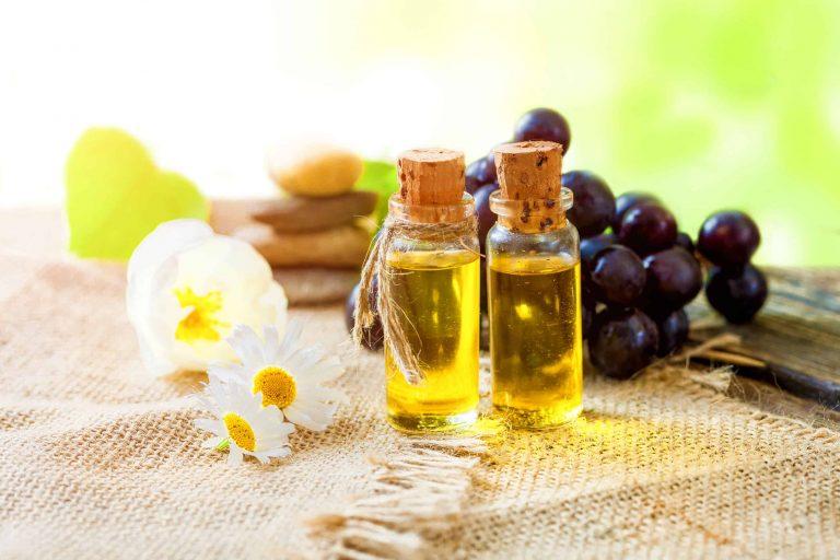 Ölfläschchen vor Trauben