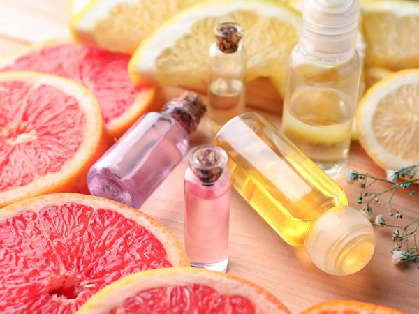 Bottles of essential oil and citrus slices on table