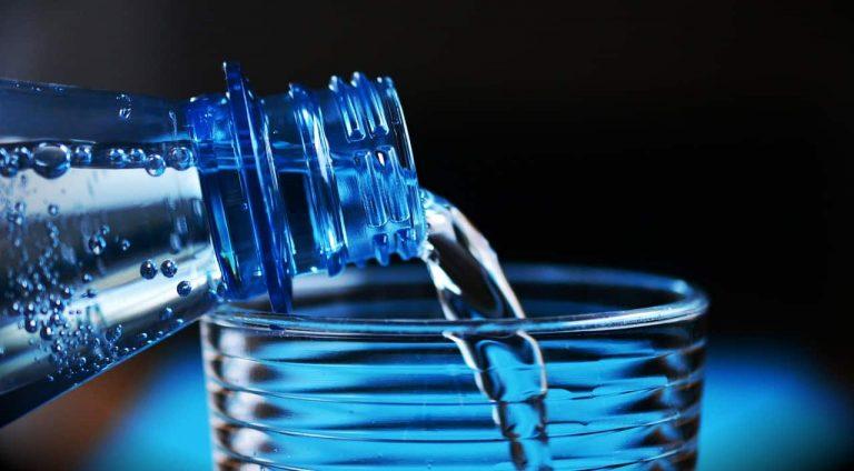 Wasser wird aus Flasche in ein Glas geschüttet