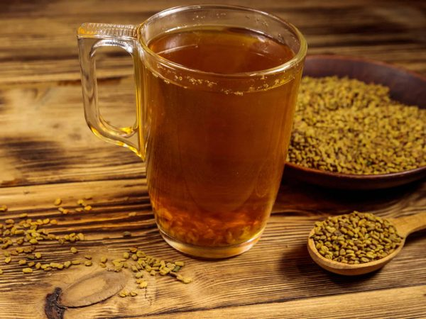 Egyptian yellow tea or Methi Dana drink and fenugreek seeds on wooden table