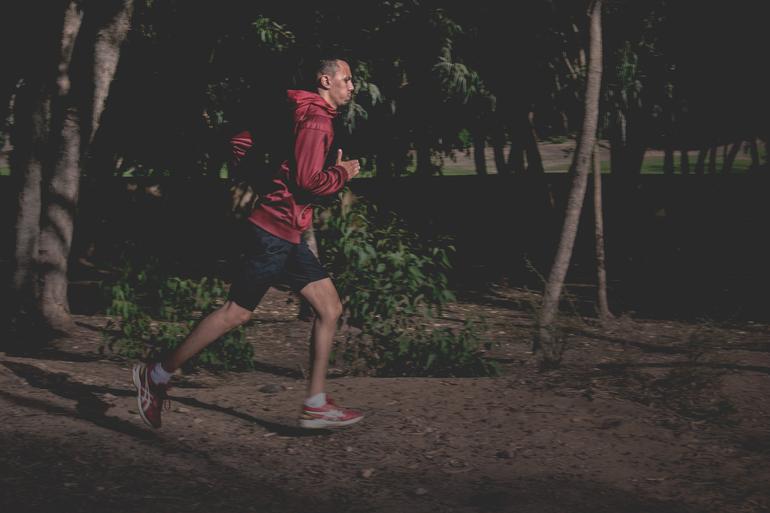Jogger mit roter Jacke und kurzer Hose auf Waldweg